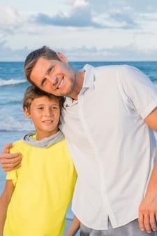 ビーチに沿って歩く幸せな父と息子の肖像画。幸せな家族、信頼と愛の概念。