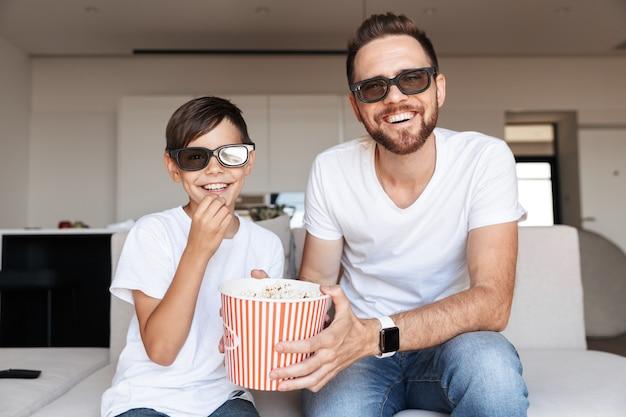 Портрет счастливых отца и сына в 3d-очках, едящих попкорн и улыбающихся, сидя на диване в помещении и смотря фильм