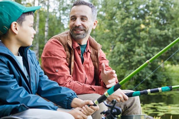 Портрет счастливого отца, наслаждающегося рыбалкой с маленьким сыном во время похода на озеро