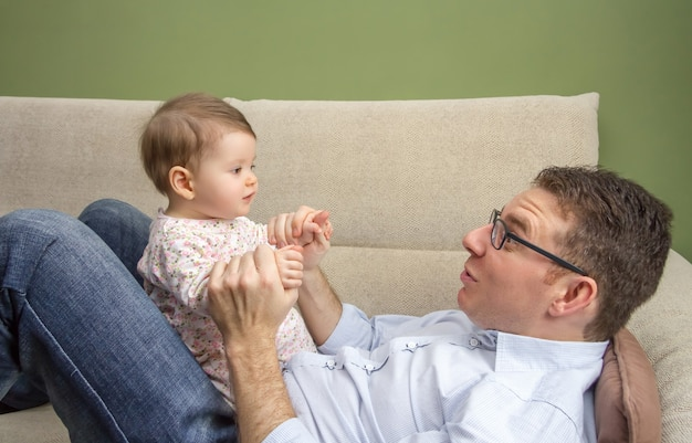 집에 있는 소파에 배 위에 앉아 있는 귀여운 아기와 노는 행복한 아버지의 초상화