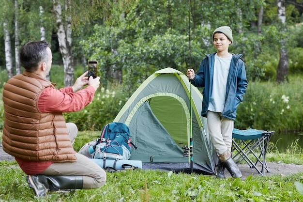 Портрет счастливого отца, фотографирующего сына, наслаждаясь вместе на рыбалке, копией пространства