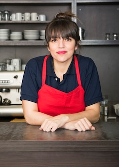 Portrait of happy female barista standing at trendy coffee shop