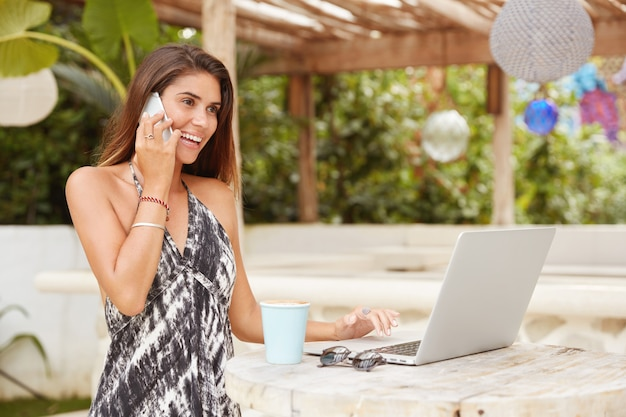 Портрет счастливой женщины расслабленно отдыхает в кафетерии на террасе, общается с кем-то через смартфон, работает на портативном компьютере, пьет латте, работает удаленно. летний отдых в кафе