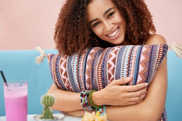 Портрет счастливой женщины с темной здоровой кожей и вьющимися волосами, обнимает подушку, чувствует себя комфортно и расслабленно в кафе, пьет фруктовый смузи, радостно смотрит на вас.