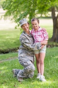 公園で彼女の娘と一緒に幸せな女性兵士の肖像画