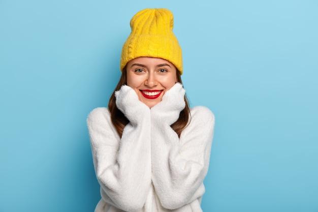 붉은 입술, 하얀 완벽한 치아, 빛나는 미소를 가진 행복한 여성의 초상화는 편안한 긴팔 스웨터를 입습니다.
