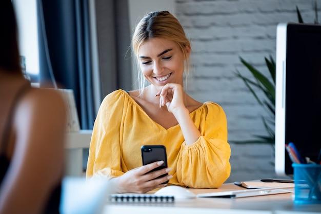 彼女のスタートアップ中小企業でコンピューターを使用している間、彼女の携帯電話でテキストメッセージを送る幸せなフリーランスのビジネス女性売り手の肖像画。