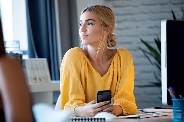 彼女のスタートアップ中小企業の窓から見ているコンピューターで作業しながら彼女の携帯電話でテキストメッセージを送る幸せなフリーランスのビジネス女性の売り手の肖像画。