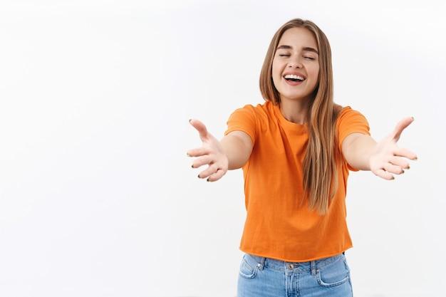 Портрет счастливой, дружелюбной веселой блондинки, протягивающей руки, чтобы обнять или обнять лучшего друга, закрыть глаза и смеясь, увидеть кого-то, кого она любит