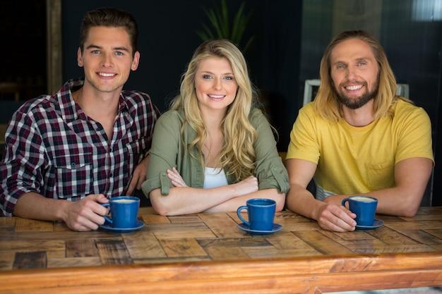 Портрет счастливых друзей, пьющих кофе за деревянным столом в кафе