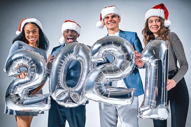 灰色の背景にメタリックシルバー2021風船と幸せな友人の肖像画。新年のお祝いのコンセプト