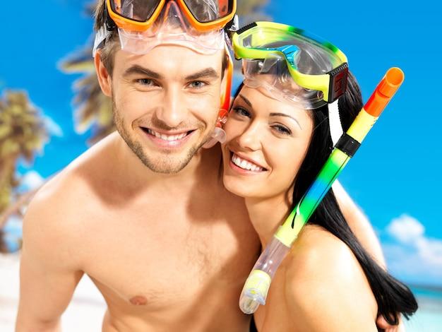 Портрет счастливой веселой красивой пары на тропическом пляже с плавательной маской на лице