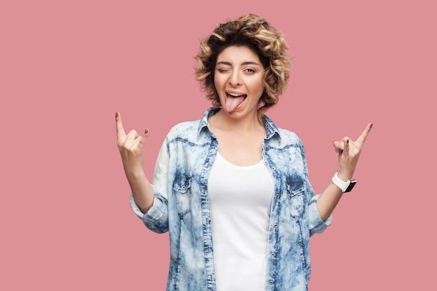 カジュアルな青いシャツを着て立って、まばたき、舌を出して、ロックホーンサインでカメラを見ている巻き毛の幸せな面白い若い女性の肖像画。ピンクの背景に分離された屋内スタジオショット。