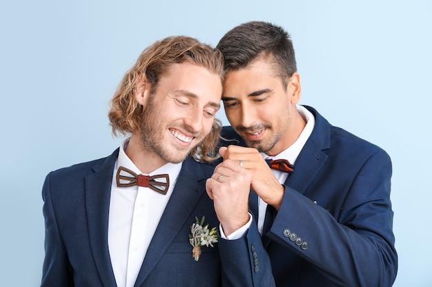 色に対して彼らの結婚式の日に幸せな同性愛者のカップルの肖像画