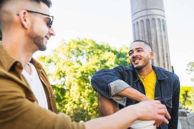 一緒に時間を過ごし、公園でデートをしている幸せな同性愛者のカップルの肖像画。 lgbtと愛の概念。