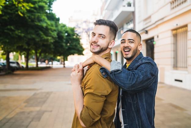 一緒に時間を過ごし、通りで抱き締める幸せな同性愛者のカップルの肖像画。 lgbtと愛の概念。