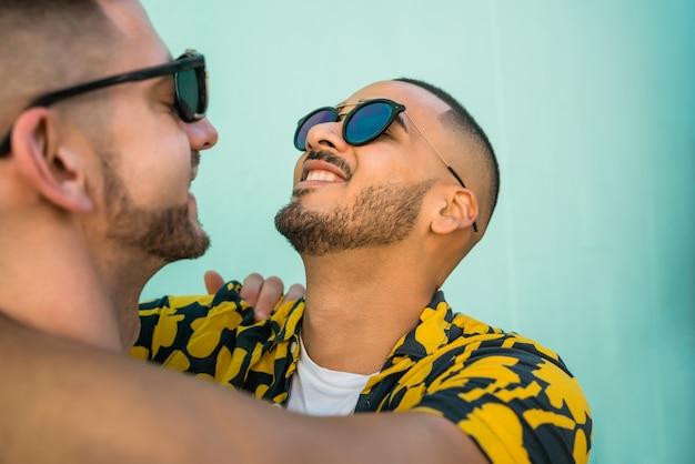 一緒に時間を過ごして、通りでハグ幸せなゲイのカップルの肖像画。