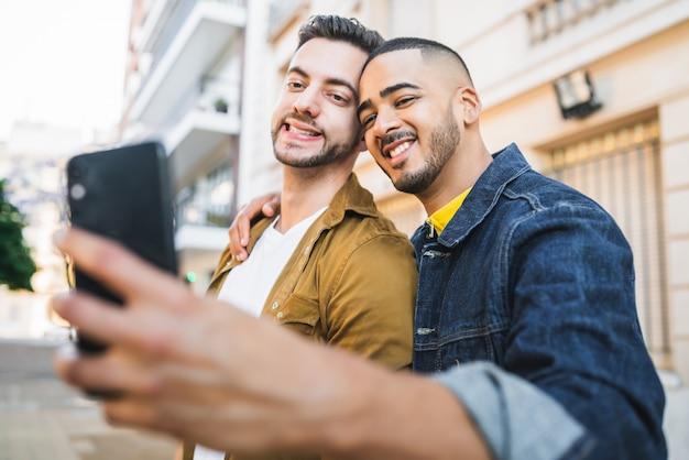 一緒に時間を過ごして、通りで携帯電話でselfieを取って幸せなゲイのカップルの肖像画。