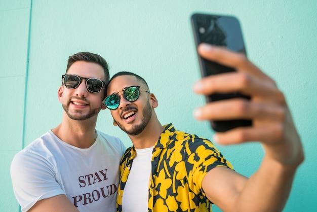一緒に時間を過ごして、携帯電話でselfieを取って幸せなゲイのカップルの肖像画。 lgbtと愛の概念。