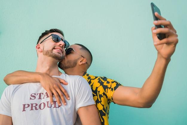 一緒に時間を過ごして、携帯電話でselfieを取って幸せなゲイのカップルの肖像画。