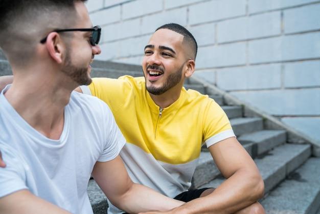 屋外の階段に座っている間一緒に時間を過ごす幸せなゲイのカップルの肖像画。