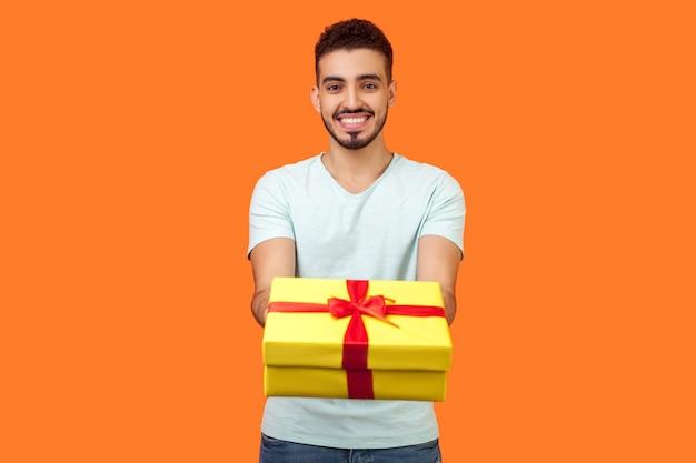 흰색 티셔츠를 입은 수염을 기른 행복한 관대한 브루네트 남자의 초상화가 웃고 카메라에 선물 상자를 주고, 휴가 선물, 자선 개념을 공유합니다. 오렌지 배경에 고립 된 실내 스튜디오 촬영