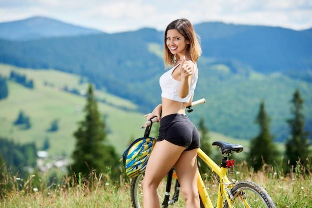 노란 산악 자전거와 함께 행복 한 여자 자전거의 초상화, 미소, 엄지 손가락을 보여주는 화창한 날을 즐기고