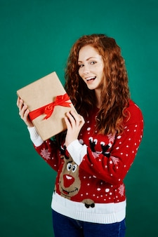 クリスマスプレゼントを保持している幸せな女の子の肖像画