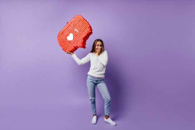 Портрет счастливой девушки в джинсах, думая об интернете. полнометражный портрет женщины брюнетки, наслаждающейся социальными сетями.