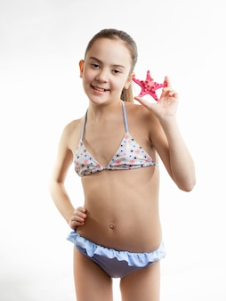 Портрет счастливой девушки в купальном костюме с красными морскими звездами