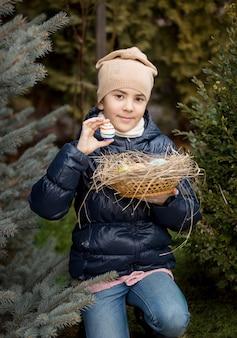 그녀가 뒤뜰에서 발견 부활절 달걀을 보여주는 행복 한 여자의 초상화