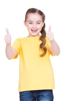 白い背景の上に分離された黄色のtシャツで親指を立てるジェスチャーを示す幸せな女の子の肖像画。