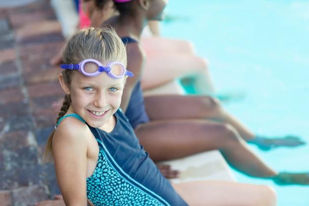 수영장에서 친구와 함께 앉아 행복 한 여자의 초상화