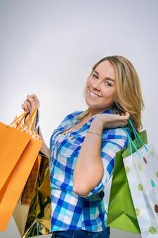 ショッピングバッグを保持している青い格子縞のシャツと幸せな女の子のティーンエイジャーの肖像画。若い消費者の概念。