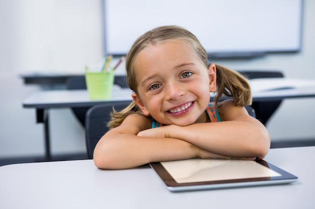教室でデジタルタブレットで幸せな少女の肖像画
