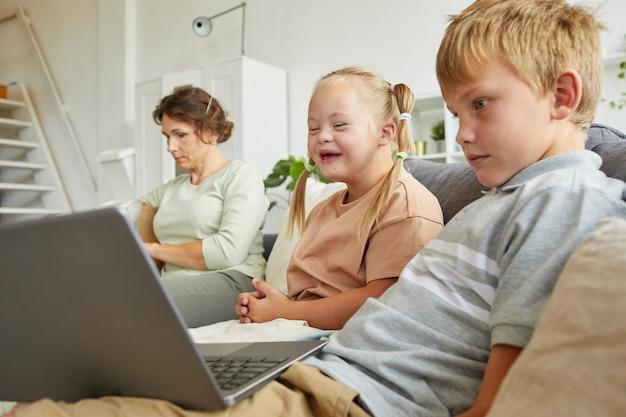 Портрет счастливой девушки с синдромом дауна, счастливо смеющейся, глядя на экран ноутбука и сидя на диване с семьей дома