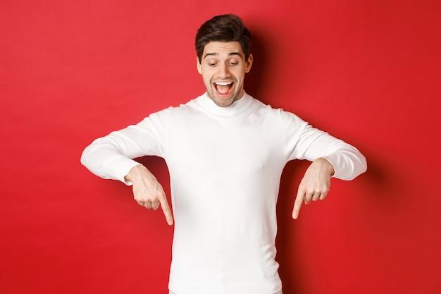 指を下に向けて興奮したsmで広告を見ている幸せな格好良い男の肖像...