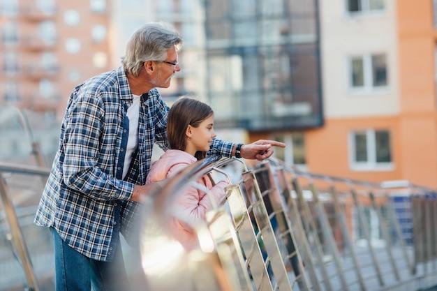 幸せな祖父と小さなかわいい女の子の肖像画は、郊外の公園で一緒にリラックスしてお楽しみください