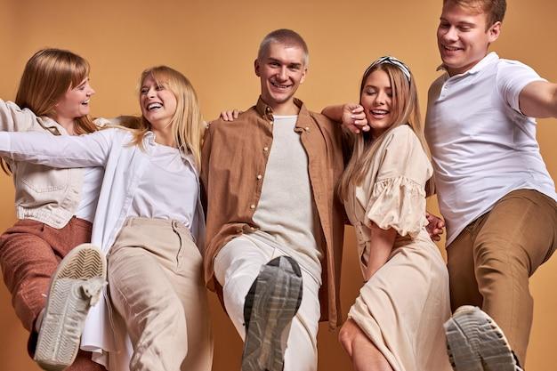 Портрет счастливой группы кавказской молодежи, развлекающейся в студии с коричневым фоном