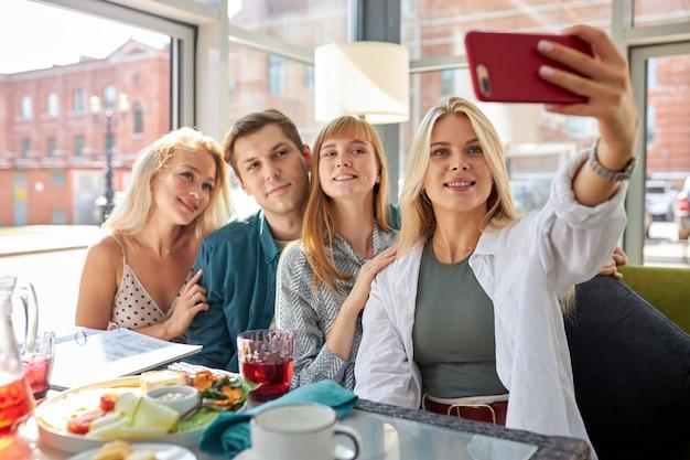 写真を撮る若い白人の友人の幸せなグループの肖像画