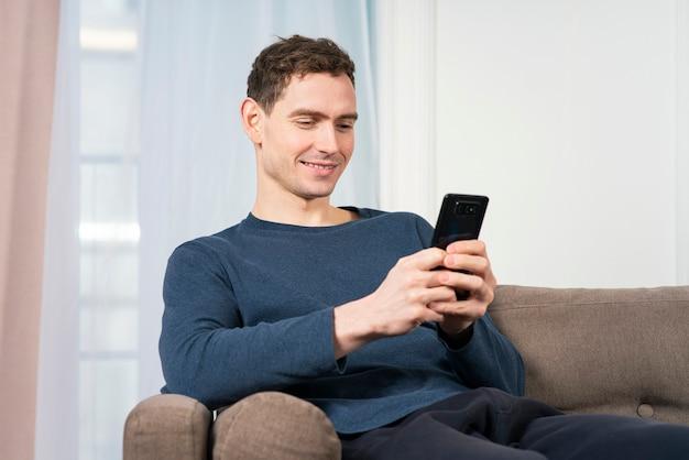 Портрет счастливого парня, молодого позитивного улыбающегося человека, использующего, глядя на экран своего мобильного телефона