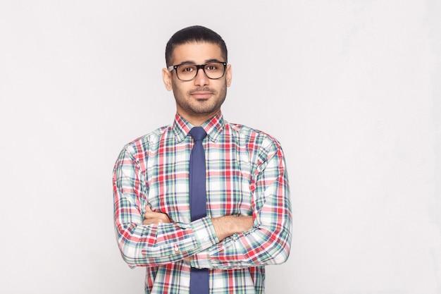 カラフルな市松模様のシャツ、青いネクタイ、交差した手に立って笑顔の黒い眼鏡で幸せなハンサムなひげを生やした実業家の肖像画。明るい灰色の背景に分離された屋内スタジオショット。