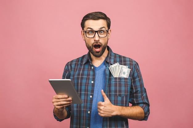 市松模様のシャツ立って、タブレットコンピューターとお金を保持している幸せなハンサムなひげを生やした若い流行に敏感な男の肖像画。ピンクの背景。いいぞ。