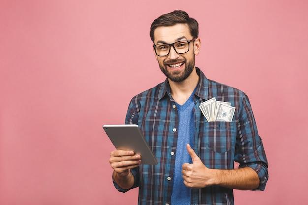 Портрет счастливого красивого бородатого молодого человека битника в клетчатой рубашке стоя, держа планшет и деньги. розовый фон недурно.