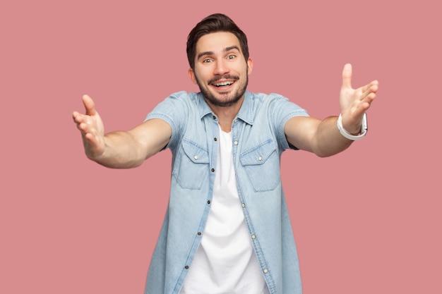 腕を上げて立って、抱きしめたいと歯を見せる笑顔でカメラを見たい青いカジュアルなスタイルのシャツを着た幸せなハンサムなひげを生やした若い男の肖像画。ピンクの背景に分離された屋内スタジオショット。