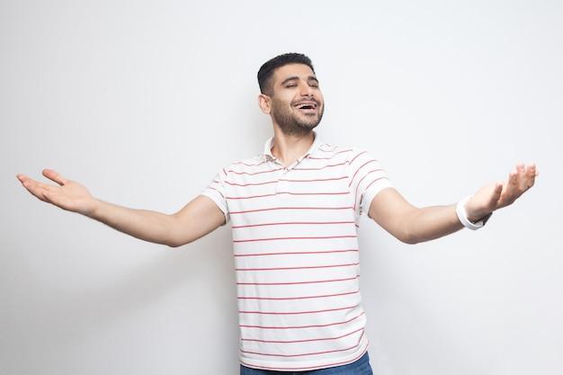 広い腕を上げて立って、歯を見せる笑顔でカメラを見ている縞模様のtシャツで幸せなハンサムなひげを生やした若い男の肖像画。白い背景で隔離の屋内スタジオショット。
