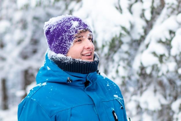 冬の雪の森で幸せなハンサムな男の肖像画
