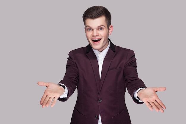 Портрет счастливого красивого молодого человека в фиолетовом костюме и белой рубашке, стоящего, смотрящего на камеру с поднятыми руками и зубастой улыбкой. крытая студия выстрел, изолированные на сером фоне.