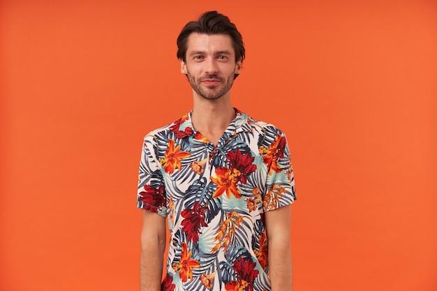 孤立したカメラを立って見ているハワイアンシャツの剛毛を持つ幸せなハンサムな若い男の肖像画