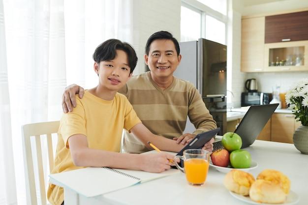 仕事や宿題をしているときに台所のテーブルに座って幸せな抱擁の父と息子の肖像画